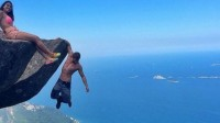 Daredevil couple hang off from a cliff edge a