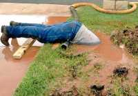 A plumber dives into muddy bog to fix a pipe
